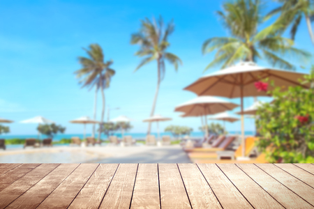 Wooden table with blurry tropical sea and resort background. 版權商用圖片