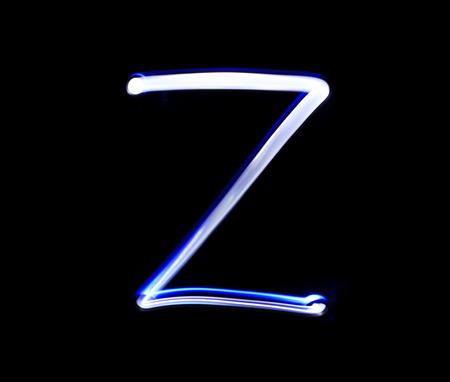 zulu: Z Zulu alphabet hand writing blue light  over black background.