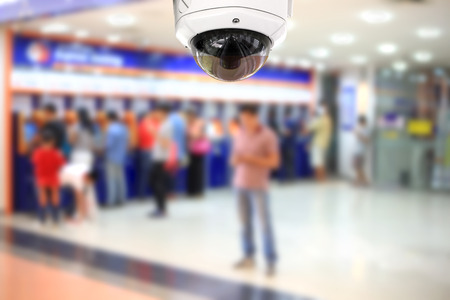 bank records: People withdraw money automatic teller machine with CCTV camera. Stock Photo