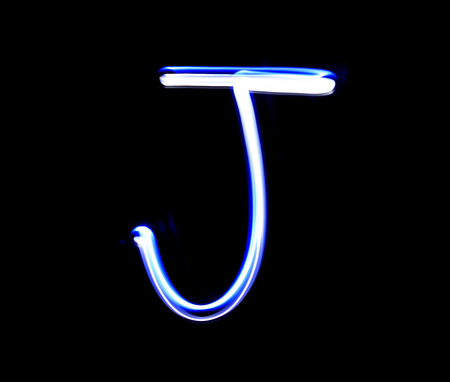 letter art: J Jimmy alphabet hand writing blue light  over black background. Stock Photo