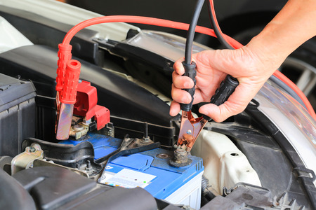 service car: Car mechanic uses battery jumper cables charge a dead battery.