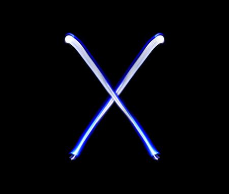 x xray: X Xray alphabet hand writing blue light  over black background.