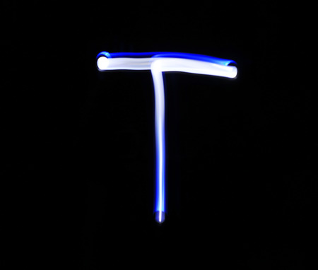 created: T Tango alphabet hand writing blue light  over black background.