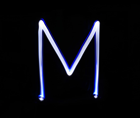 neon letter: M Mike alphabet hand writing blue light  over black background. Stock Photo