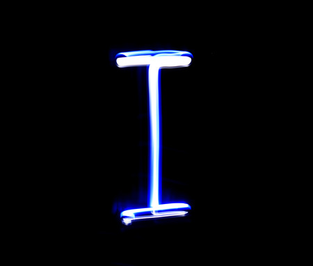 letter art: I Item alphabet hand writing blue light  over black background.