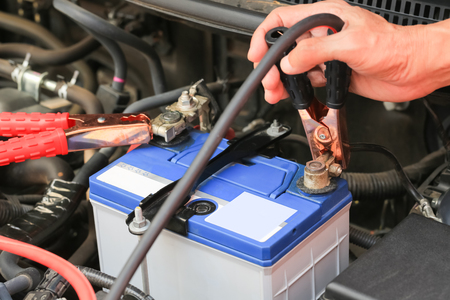 motors: Car mechanic uses battery jumper cables charge a dead battery.