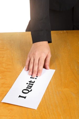 resignation: Hand holding resignation letter on the desk of the boss. Stock Photo