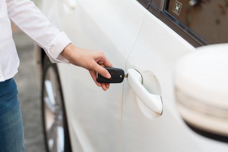 robo de autos: Mano femenina abrir el coche blanco en el sistema automático de llaves.