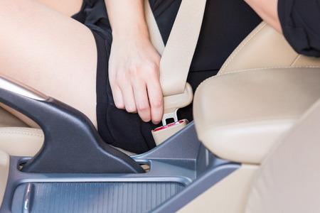 fastening: Women hand fastening seat belt inside car. Stock Photo