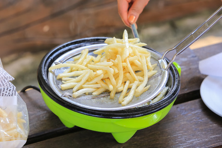 friture: French fries cooking on deep fryer.