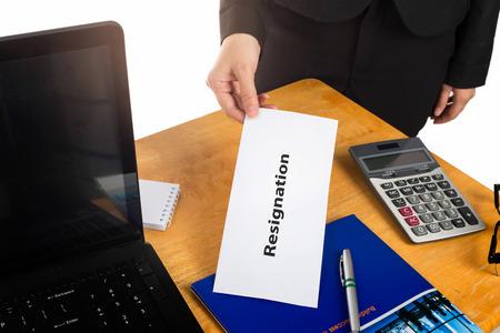 Mano que sostiene la carta de renuncia en el escritorio del jefe.