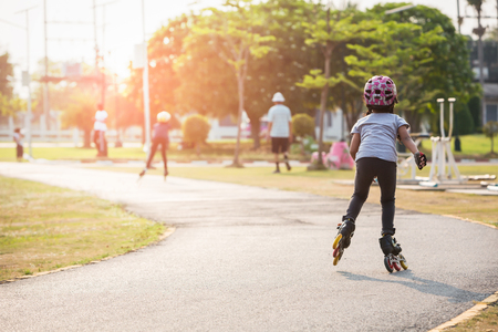 rollerblades: Young couples roller skates outdoor in park. Stock Photo