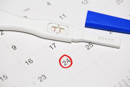 conceive: Positive pregnancy test with calendar.