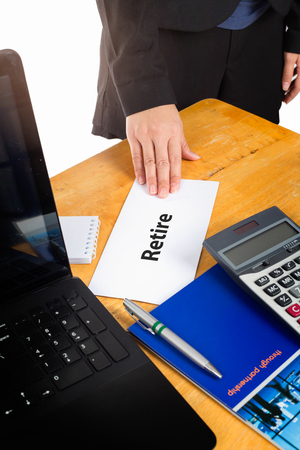 retire: Hand holding retire letter on the desk of the boss.