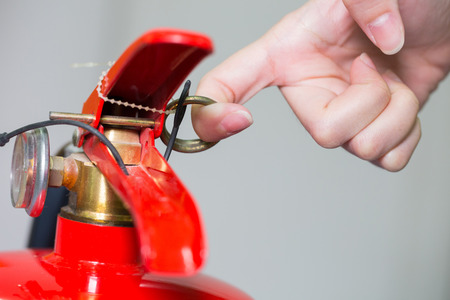 compressed air hose: Close- up Fire extinguisher and pulling pin on red tank. Stock Photo