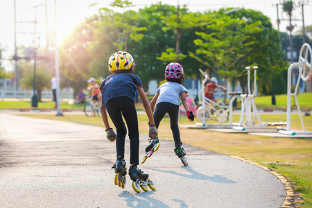 roller: Young couples roller skates outdoor in park. Stock Photo