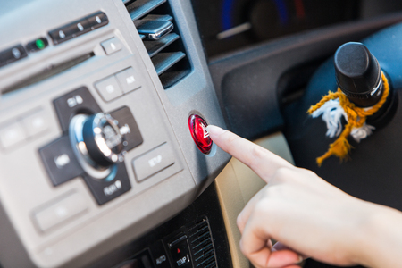 control panel lights: Female hand pressing emergency light button on car dashboard. Stock Photo