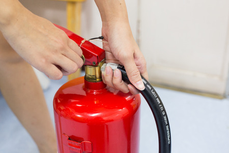 Close- up Fire extinguisher and pulling pin on red tank. Stock Photo