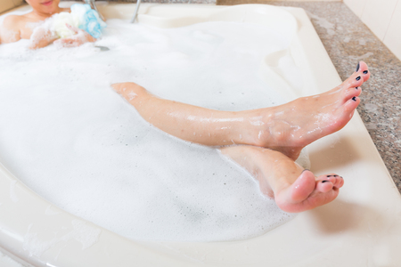 girls bathing: Beautiful girl showering and washing legs in bathtub. Stock Photo