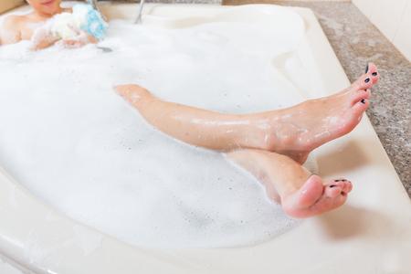personas banandose: ducharse chica hermosa y lavado de las piernas en la bañera.