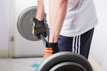 weightlifting gloves: Man of weightlifter for barbell exercise. Stock Photo