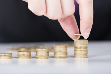 fill up: Close up male hand fill money stack on gold coins bar.