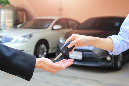 handing over: Female hand giving a key for buyer or rental car.