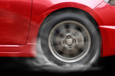 burns: Red car racing spinning wheel burns rubber on floor. Stock Photo