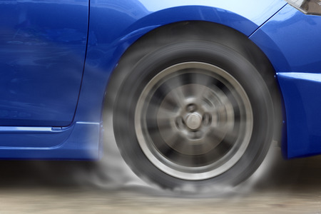 burnout: Blue car racing spinning wheel burns rubber on floor.