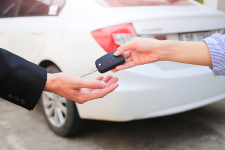 handing over: Business hand giving a key for buyer or rental car.