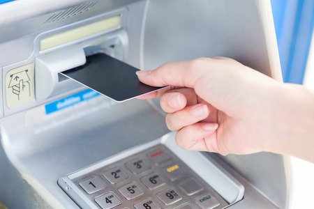 automatic transaction machine: Close up hand inserting card into ATM. Foto de archivo