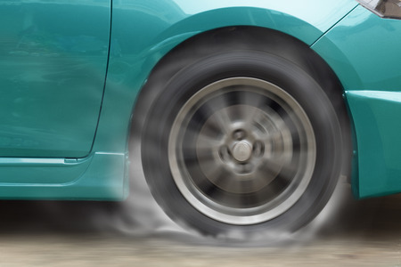 burns: Green car racing spinning wheel burns rubber on floor.