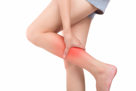 Woman with calf feeling pain on white background Stock Photo