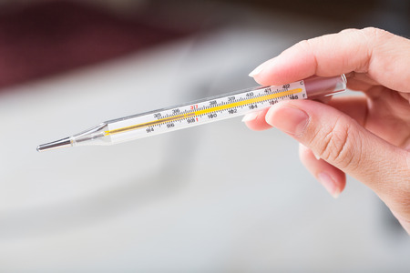 termometer: Close-up hand holding on thermometer for checking patient. Stock Photo