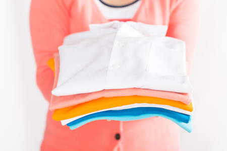 completion: House wife holding clothes on white background.