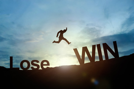 Silhouette of businessman glowing jump Lose to Win. success concept