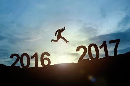 輝くビジネスマンのシルエットは、2017 年まで 2016 をジャンプします。成功のコンセプト 写真素材