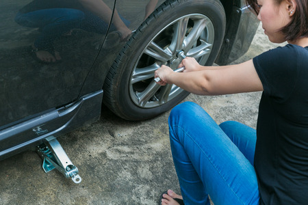 female driver: Female driver changing tyre on her broken car.