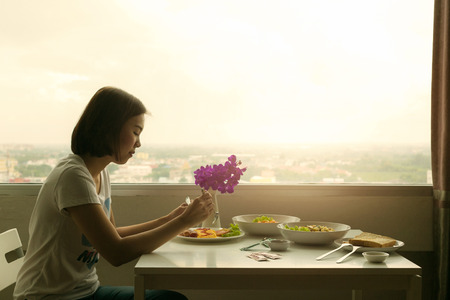 Pensive young woman dinner alone in the room. Stockfoto