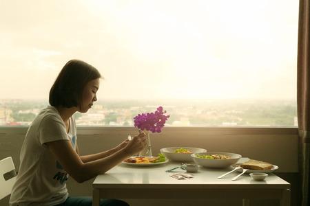 Pensativo mujer joven y la cena solo en la habitación.