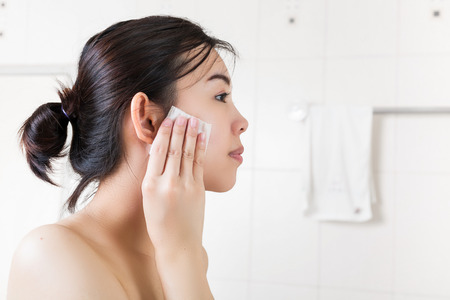 Beautiful woman removing makeup from her face in bathroom. Stock Photo