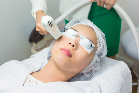 Close-up of Beautician Giving Laser Epilation Treatment To Young Woman Face. Фото со стока