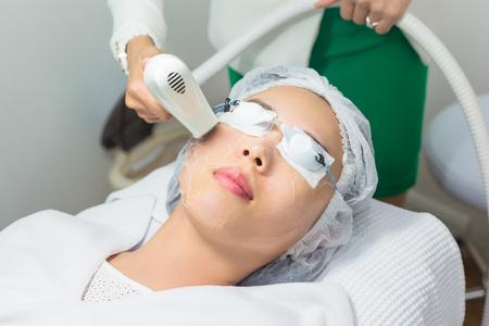 Close-up van schoonheidsspecialist die laserepilatie geeft aan het jonge gezicht van de vrouw. Stockfoto