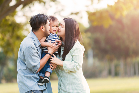 Happy mother and father kissing his little son in park Banque d'images