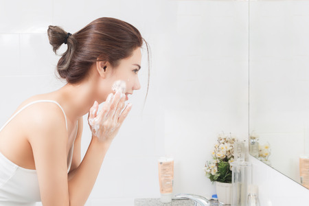 Woman happy cleanses the skin with foam in bathroom. Stock Photo