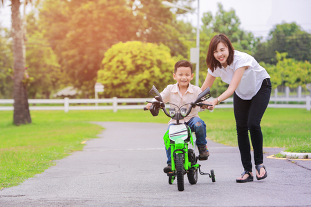 Loving mother help her cute son ride a bicycle. Stock Photo