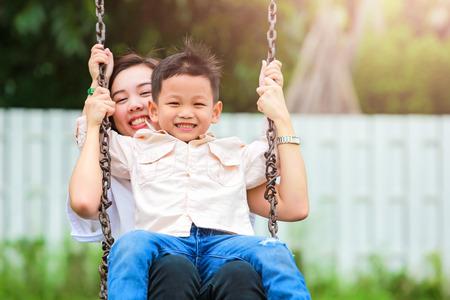 Happy family having fun on a swing ride at a garden. Stockfoto