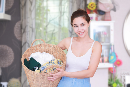 Smiling housewife posing with basket with clean laundry.