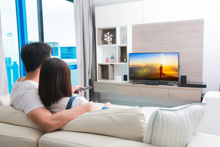 Happy family watches television while sitting on the sofa. Stockfoto