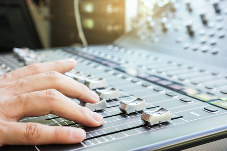 Hand adjusting audio mixer console buttons, faders and sliders. Stock Photo